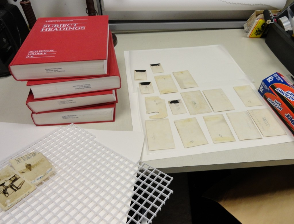 Carefully placing the humidified photos onto a blotter covered with wax paper. Another blotter goes on top.