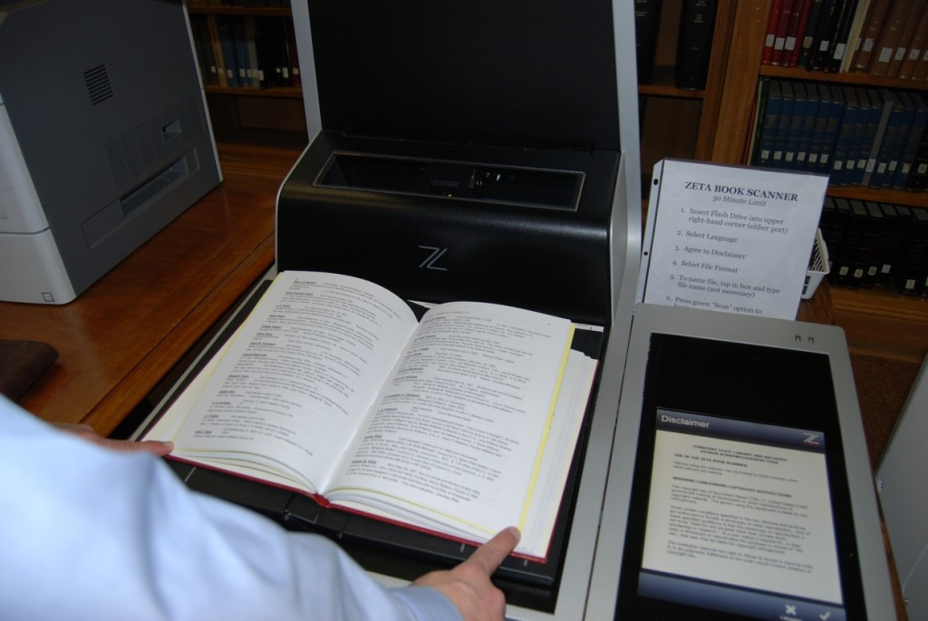 The amazing Zeta Book Scanner. You can scan the book face up, thereby protecting the spine from the pressure of flattening the open book onto the glass bed. There is a scan button built into the bed so you don't have to let go of the book. You really have to see one of these in person.