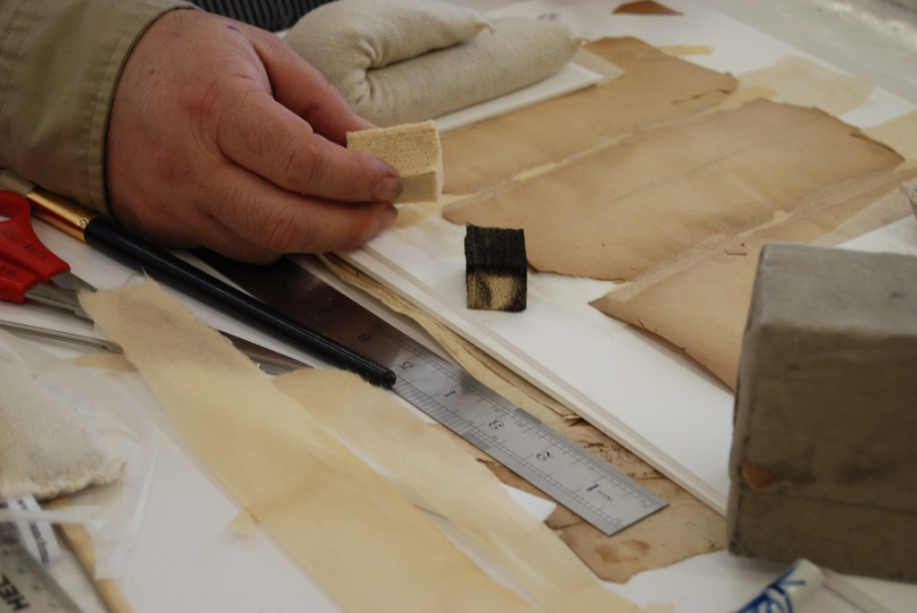 A conservator removing dirt from a document. notice that one cleaning sponge is already black with dirt.