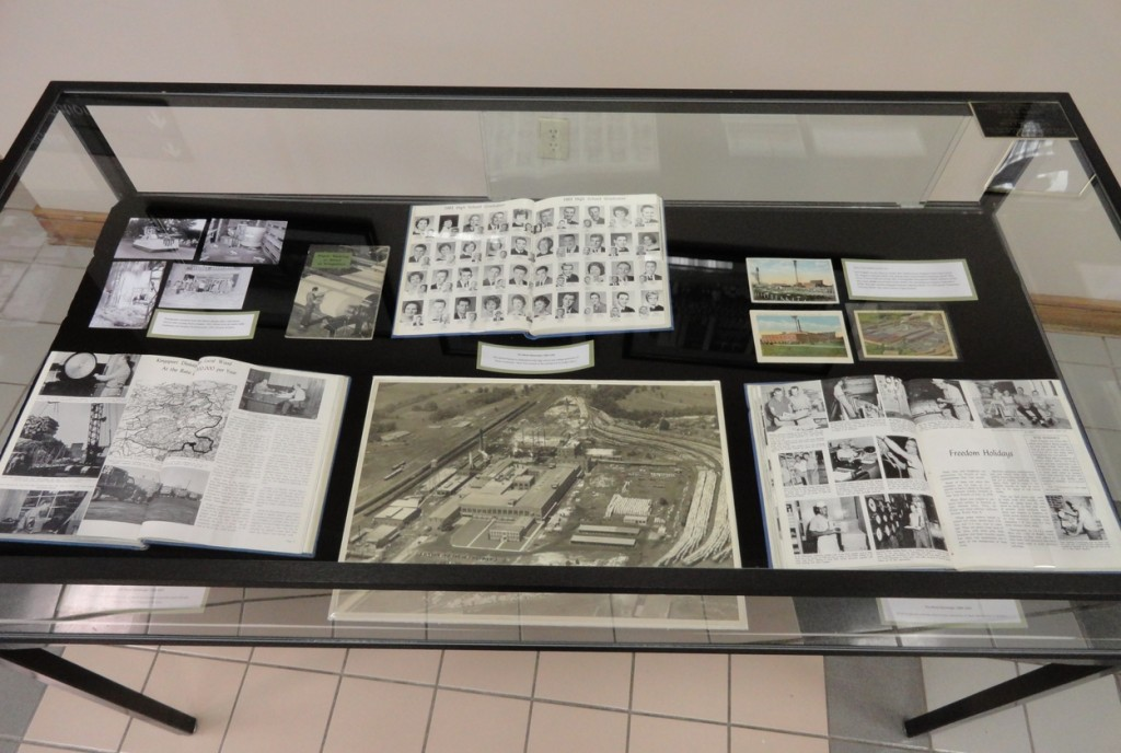 The exhibit case on the left boasts a 1938 Richard Alvey aerial image of the plant and three vintage postcards.