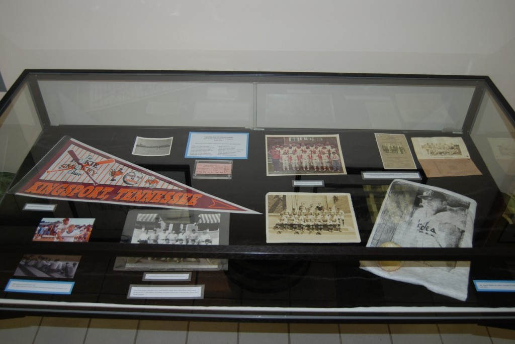 The right case showcases a Hokie Smokey Classic pennant, a 1972 team photo from Sevier Middle School, and a 1930 community league banquet program.
