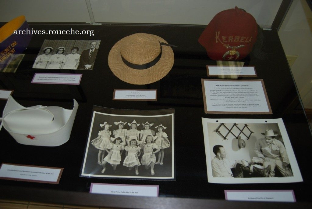 A close-up of the right case focuses on a nurse's cap from the archives' extensive Red Cross collection and a fez from the Huffaker Family Collection, KCMC 75.