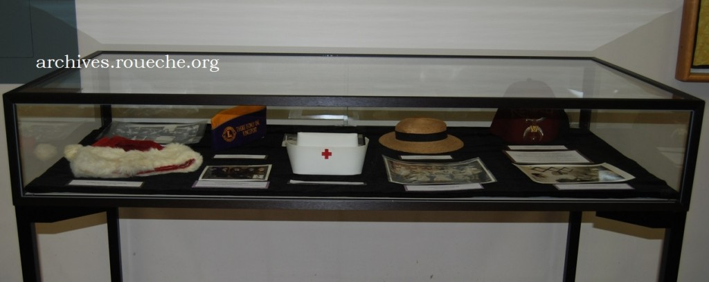 The right exhibit case features the oldest hat on display, a 1910 child's straw hat once belonging to Ruby Netherland.