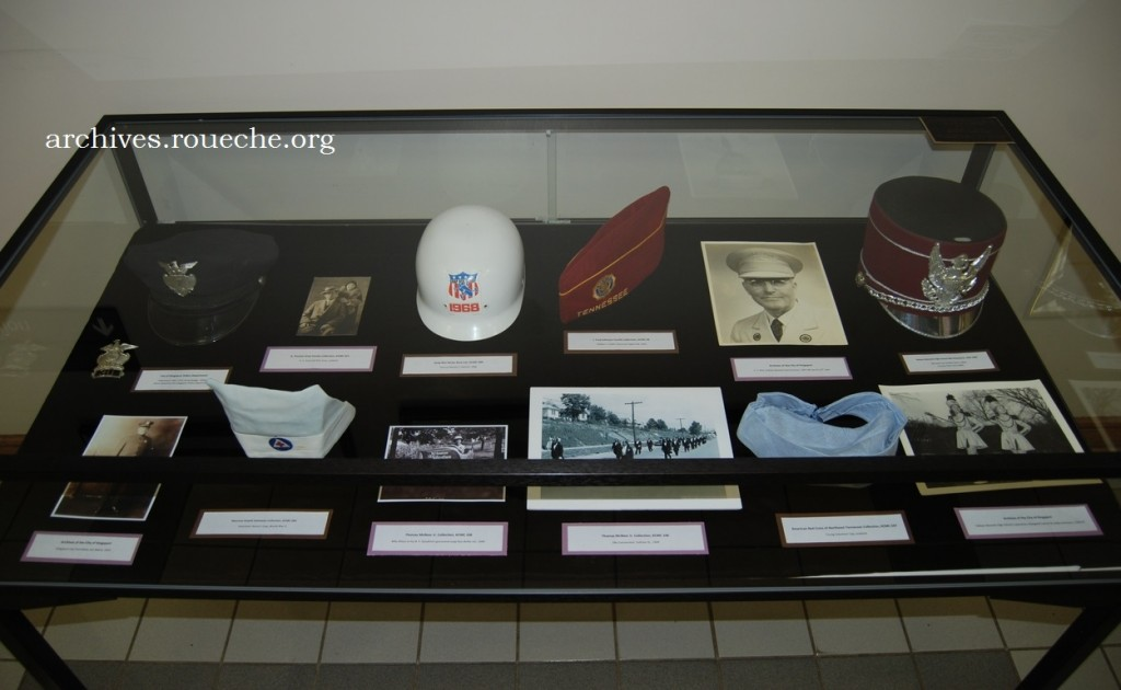 Items in the left case feature Tommie Mottern's 1968 soap box derby helmet and Maurine Hattaway's nursing cap from World War II.