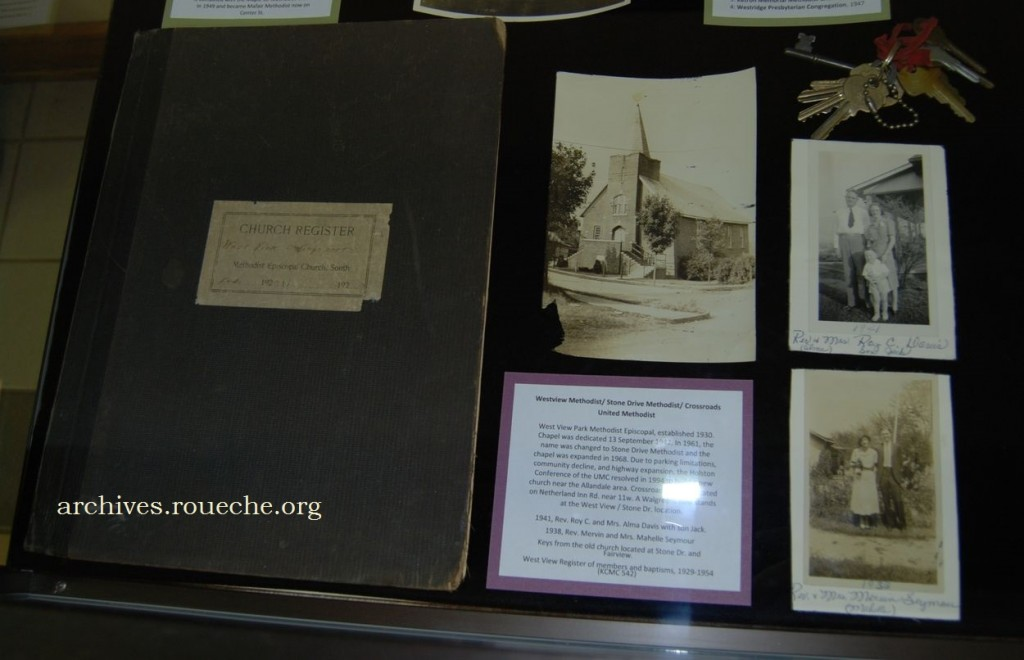 Items in the exhibit include the church's first register, photographs of early ministers, and an original photograph of the first chapel.