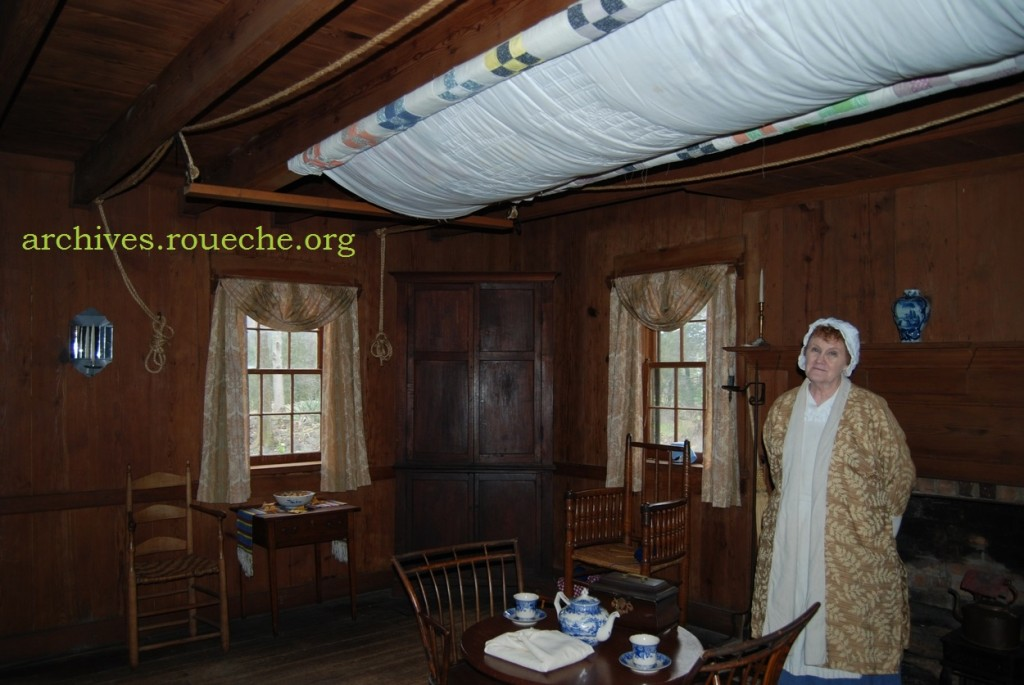 in the great room, a costumed interpreter points out the quilting frame and explains the availability of food stuffs to early settlers.